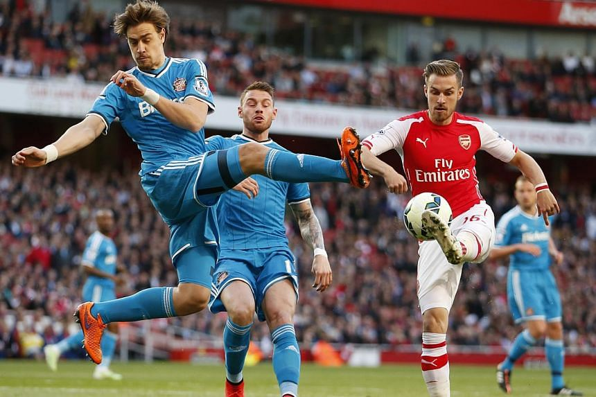 Sunderland defender Sebastian Coates (left) attempts to win the ball from Arsenal midfielder Aaron Ramsey (right) in their 0-0 draw at the Emirates Stadium in London. -- PHOTO: REUTERS