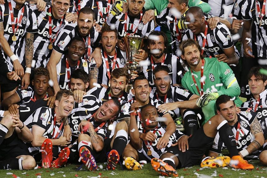 Juventus players celebrating with the Italian Cup trophy after a 2-1 win over Lazio at the Stadio Olimpico in Rome. -- PHOTO: REUTERS