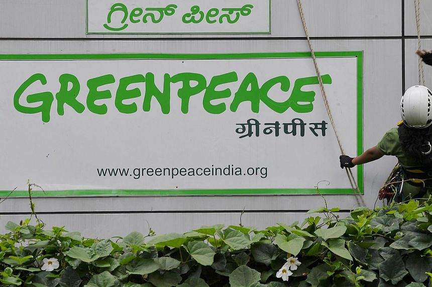 Activists of GreenPeace rappel down their office building to unfurl banners that read 'democracy' and 'freespeech' in Bangalore on May 15, 2015. Greenpeace is determined to keep operating in India even after the federal government froze its bank acco