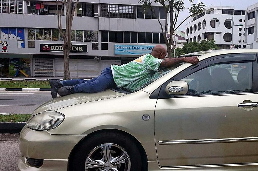 Mr Haresh Govindaraju clinging on to the windscreen of the car driven by Murali Krishnan Naidu, who was fined $2,000 and banned from the road for nine months. -- PHOTO: LIANHE ZAOBAO