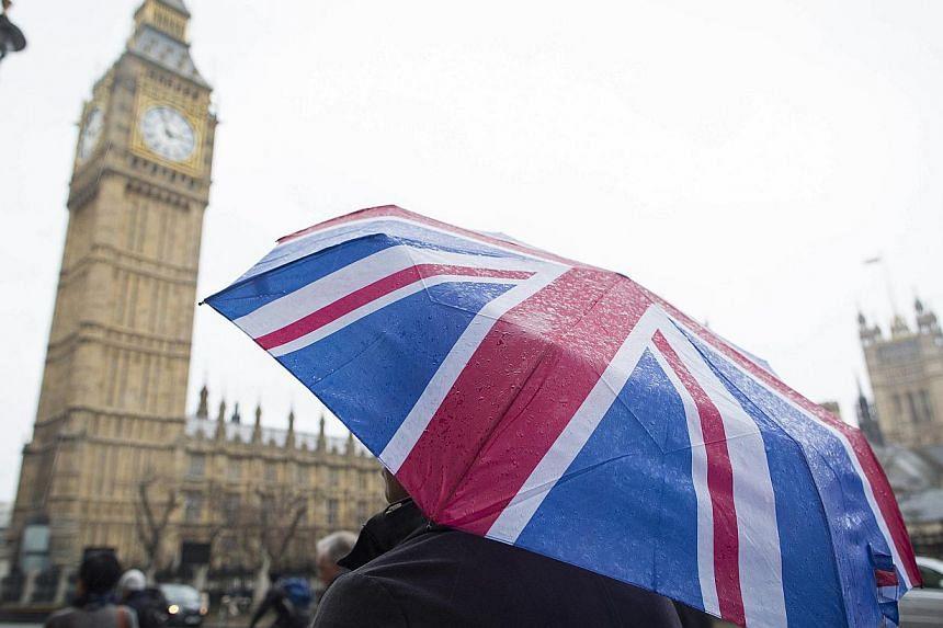 A tourist sheltering from the rain beneath a Union flag-themed umbrella, near the Houses of Parliament and the Elizabeth Tower in London on Jan 12, 2015. London received a record number of foreign visitors in 2014, with 17.4 million tourists flooding
