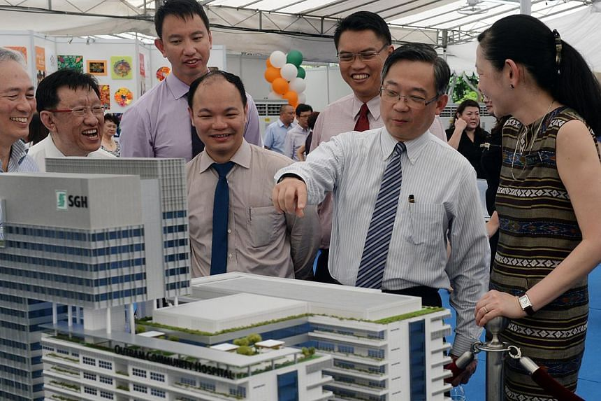 Health Minister Gan Kim Yong (second from right) with SingHealth CEO Ivy Ng (far right) looking at a model of Outram Community Hospital, due to be completed by 2020, at the groundbreaking ceremony on May 21, 2015. -- ST PHOTO: AZIZ HUSSIN