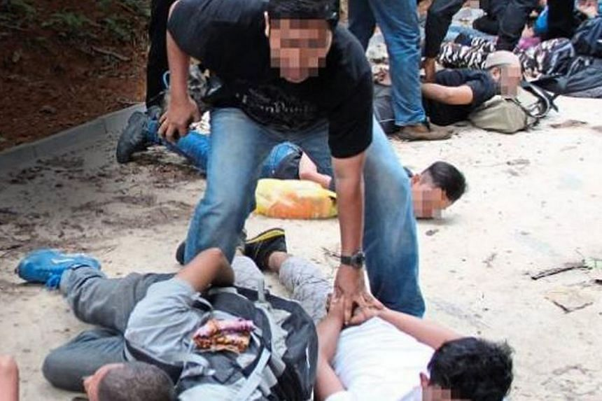 Bukit Aman's Special Branch Counter Terrorism Division detaining 11 men at the foothills of Hutan Lipur Gunung Nuang on April 25, 2015. -- PHOTO: THE STAR