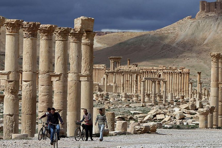 A file picture taken on March 14, 2014, shows Syrian citizens riding their bicycles the ancient oasis city of Palmyra, 215km north-east of Damascus. -- PHOTO: AFP