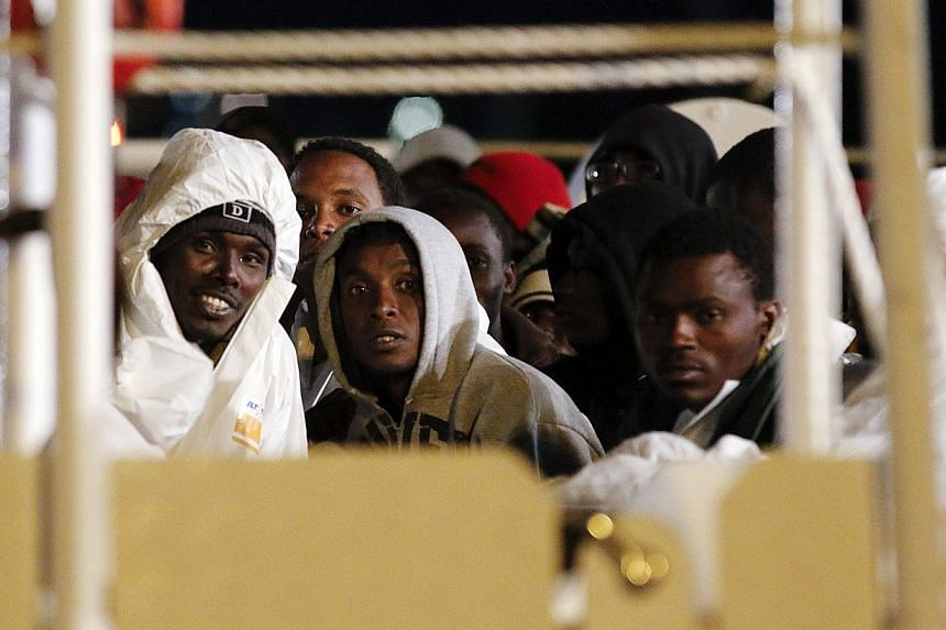 Migrants wait aboard a navy ship before being disembarked in the Sicilian harbour of Augusta on March 4, 2015.The arrest in Italy of a terror suspect posing as a boat migrant has fuelled nightmare scenarios of Islamic militant infiltration of E