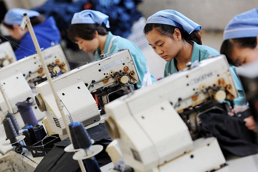 Workers producing clothes in a factory in Huaibei, east China's Anhui province, on May 19, 2015. China's factory activity contracted for the third straight month in May, which together with a lacklustre performance from Japan and alarmingly weak expo