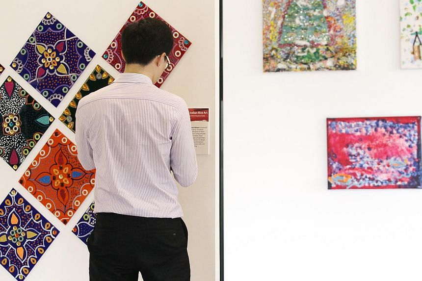 A man looking at pieces from the Batik Painting Project, which was organised by the Cerebral Palsy Association Singapore. -- PHOTO: LIANHE ZAOBAO