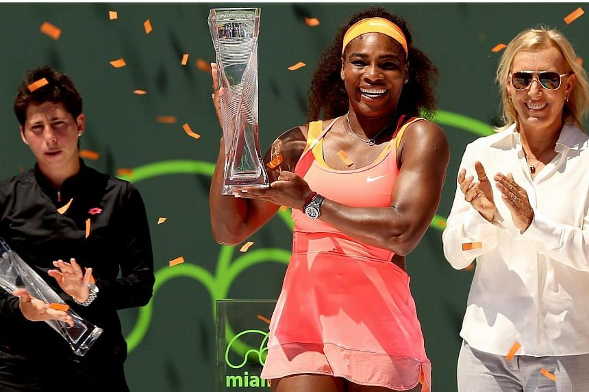 Flanked by Carla Suarez Navarro of Spain and Martina Navratilova, Serena Williams poses with the Butch Buchholz Trophy after defeating Navarro during the final on day 13 of the Miami Open Presented by Itau at Crandon Park Tennis Center on April 4, 20
