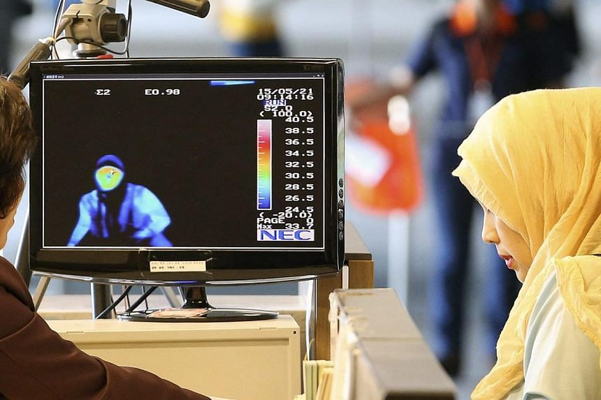 Arriving passengers from the Middle East pass by a thermal camera at Incheon airport, west of Seoul, South Korea, on May 21, 2015.South Korean health officials confirmed the country's third case of Middle East Respiratory Syndrome (Mers) on Thu