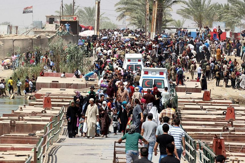 Iraqi residents from the city of Ramadi, who fled their homes as Islamic State militants tightened their siege on the last government positions in the capital of Anbar province, wait to cross Bzeibez bridge, on the southwestern frontier of Baghdad, o