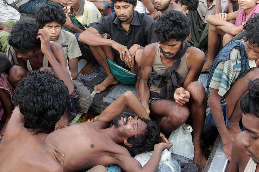 Rohingya migrants sit in a boat off the coast near the city of Geulumpang in Indonesia's East Aceh district of Aceh province before being rescued on May 20, 2015. -- PHOTO: AFP