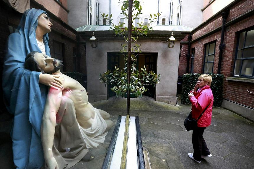A woman prays in front of a statue of Mary and Jesus in the Grafton street area of Dublin in Ireland May 19, 2015. -- PHOTO: REUTERS