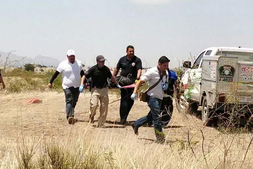 Mexican forensics carrying the dead body of a six-year old child, who was killed by minors, in Chihuahua state, Mexico, on May 19, 2015. -- PHOTO: EPA