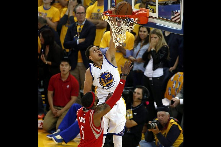 Golden State Warriors guard Stephen Curry (centre) dunking the ball over Houston Rockets forward Josh Smith (left) during the second half of their NBA Western Conference Finals in California, on May 19, 2015. The Warriors edged Houston Rockets 99-98