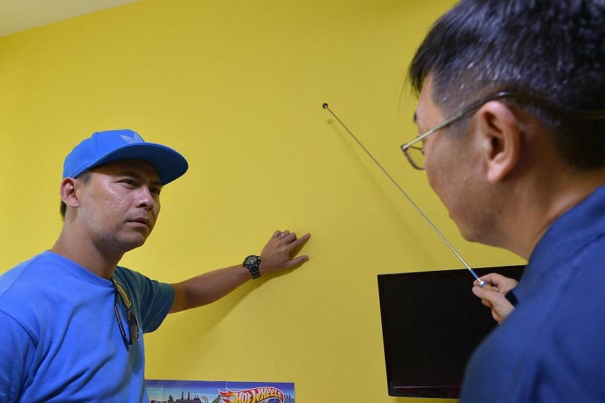 Security officer Mohamad Rizan Mazlan pointing out cracks on a wall in his Waterway Banks flat to a professional home inspector. Other residents in the estate say they have spotted cracks on their walls too.