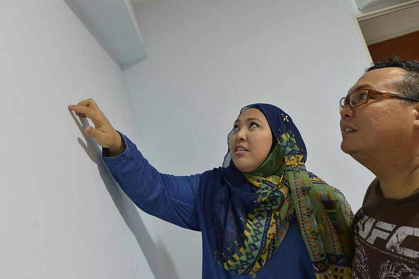 Ms Mazuwina Mohamad, 34, and her husband, Mr Jumani Samat, 35, pointing out cracks in the wall of their Punggol flat. -- ST PHOTO: ALPHONSUS CHERN