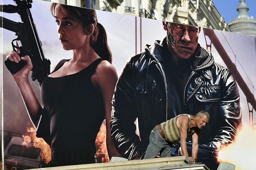 A worker is seen in front of a poster of Terminator Genisys showing cast members Arnold Schwarzenegger (right) and Emilia Clarke (left) at the Carlton Hotel, ahead of the 68th Cannes Film Festival, in Cannes, France, 12 May 2015. -- PHOTO: EPA