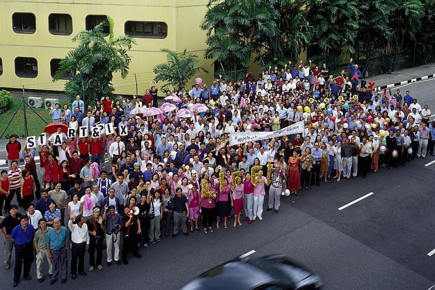Straits Times staff gather for a group shot outside the Times House in 2002, days before the ST newsroom moved to Toa Payoh North. The iconic building had housed the ST office for more than four decades. On July 18 and 19, ST is hosting a reunion of