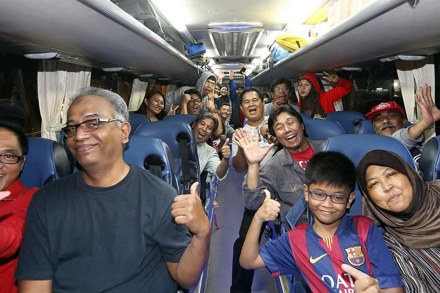 Some of the 3,000 LionsXII supporters cheering yesterday as they were about to leave for Kuala Lumpur for tonight's Malaysian FA Cup final, the first for the Singapore club.