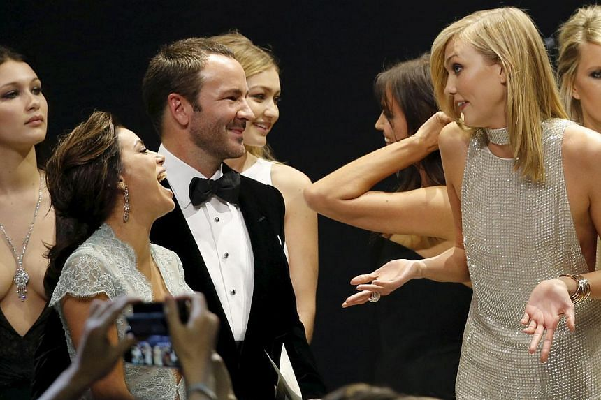US actress Eva Longoria (second left) and US fashion designer Tom Ford (third left) joke with US model Karlie Kloss (second right) as they conduct an auction during the Cannes Aids fund-raiser on May 21, 2015. -- PHOTO: REUTERS
