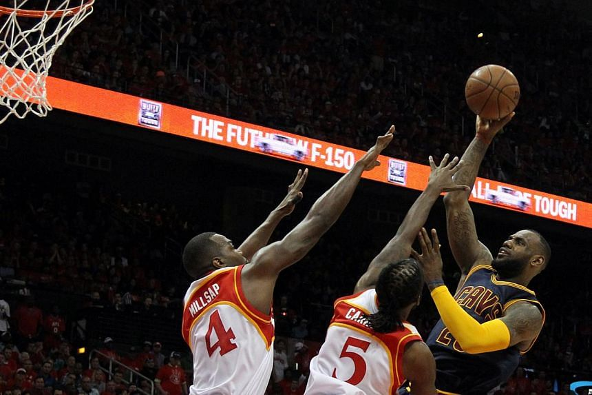 Cleveland Cavaliers forward LeBron James (right) shoots against Atlanta Hawks forward DeMarre Carroll (centre) and forward Paul Millsap (left) during the second quarter in game two of the Eastern Conference Finals of the NBA Playoffs at Philips Arena