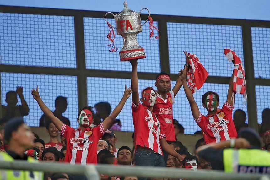 Kelantan fans holding a home made FA cup trophy at the Malaysia FA Cup final 2015 between the Kelantan FA and LionsXII held at the Bukit Jalil National Stadium on May 23, 2015. -- ST PHOTO: NEO XIAOBIN