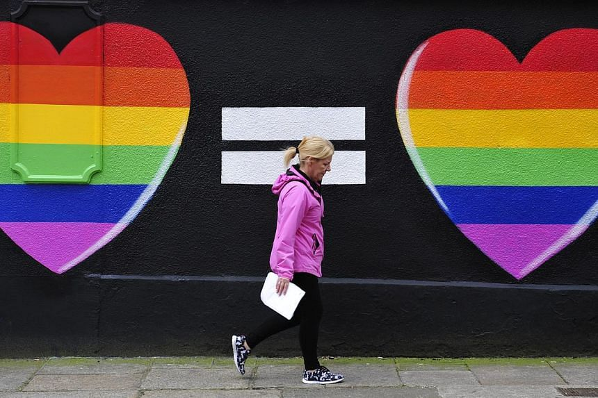 A woman walking past a mural of two hearts painted in rainbow colours in Dublin on May 22, 2015. -- PHOTO: EPA