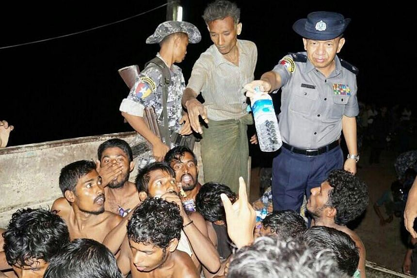 A Myanmar police officer giving a water bottle to would-be migrants on a fishing boat off the western coast of Rakhine on May 22, 2015. -- PHOTO: AFP/MYANMAR INFORMATION MINISTRY