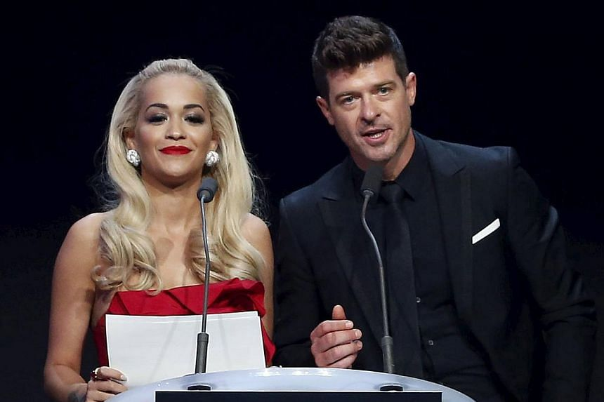 British singer Rita Ora (left) and US singer Robin Thicke conduct an auction during the Cannes Aids fund-raiser on May 21, 2015. -- PHOTO: REUTERS