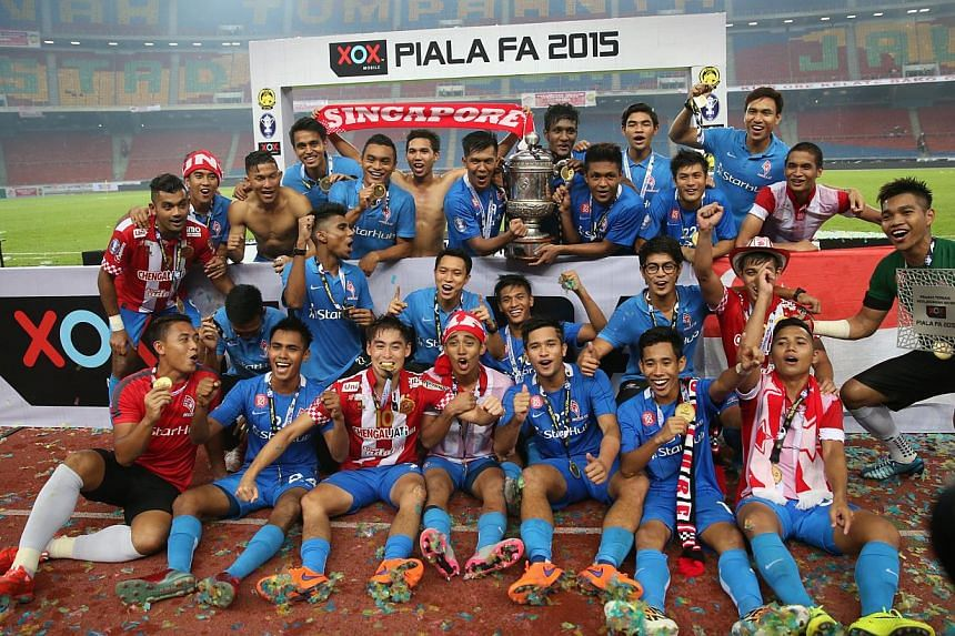 The LionsXII players celebrating with the Malaysian FA Cup after their 3-1 victory over Kelantan. -- ST PHOTO: NEO XIAOBIN