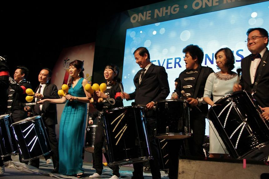 NHG group chief executive Philip Choo (fourth from right) and senior management drumming on stage during the celebrations. -- PHOTO: NHG