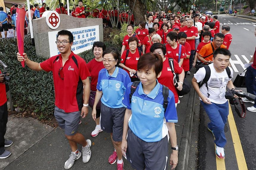 National sailor and SEA Games debutant Colin Cheng (second from left) holds a replica of the games torch (which is passed around during the walk) leads an estimated 800 Tanjong Pagar GRC residents on a 1km walk round Telok Blangah Crescent in support