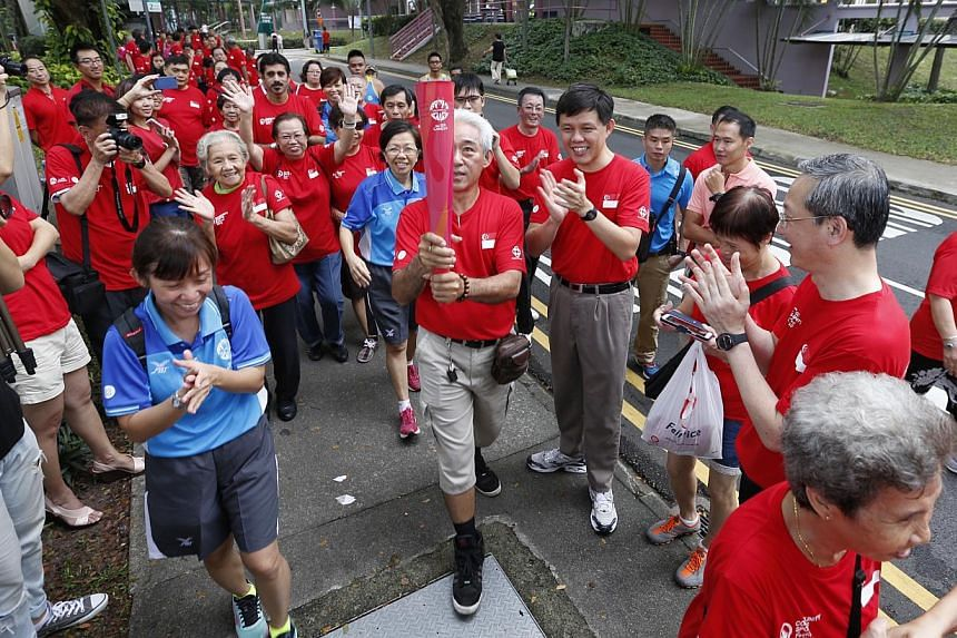 Mr Chng Hung Cher, a driver in his 60s, holds a replica of the SEA Games official torch as he and other Tanjong Pagar GRC residents, cheered on by grassroots advisers Chan Chun Sing, Indranee Rajah (not in picture), and Sam Tan, return on the final s