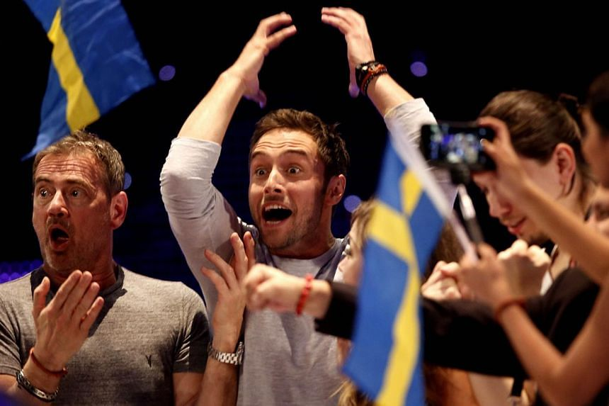 Sweden's Mans Zelmerlow (centre) celebrates winning the 60th Eurovision Song Contest final on May 23, 2015 in Vienna. -- PHOTO: AFP