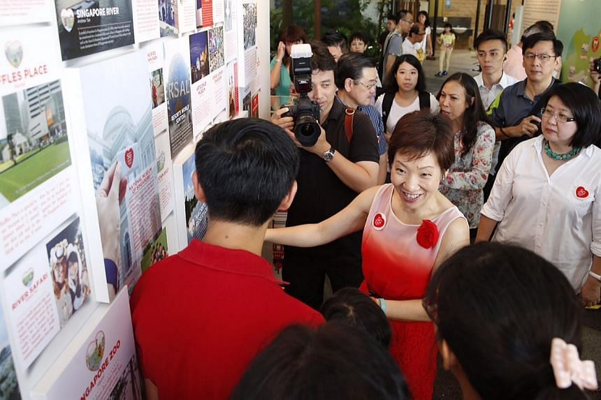 Minister in the Prime Minister's Grace Fu (centre), who is the co-chair of the SG50 Environment and Infrastructure Committee overseeing the SG Heart Map project, touring an exhibition with the unveiling of the 50 SG Heart Map places at Sentosa Siloso