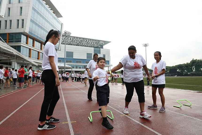 Maximus Lee How Zer, seven, from MINDS Woodlands Gardens School playing the Ketupat Race during a sports event to mark Singapore's golden jubilee at theInstitute of Technical Education College Central on May 23, 2015. He is being cheered on by