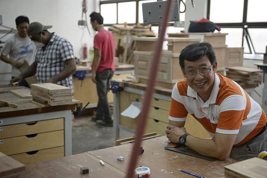 Printing veteran Lee Kok Kee may have taken a big pay cut, but the 53-year-old says he has a lot of satisfaction from working with his hands. -- ST PHOTO: MARK CHEONG