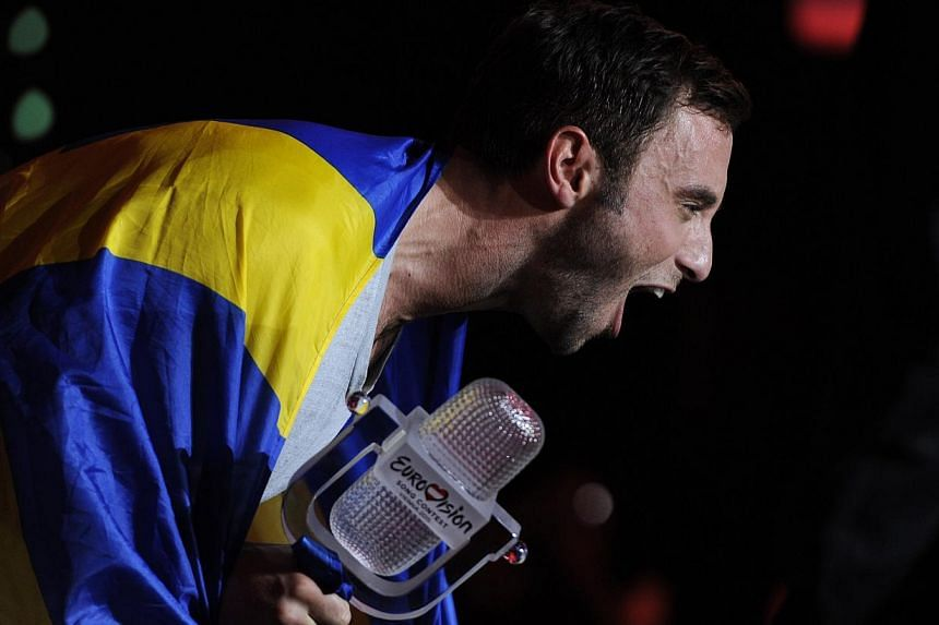 Sweden's Mans Zelmerlow holds the trophy after winning the Eurovision Song Contest on May 23, 2015 in Vienna. -- PHOTO: AFP