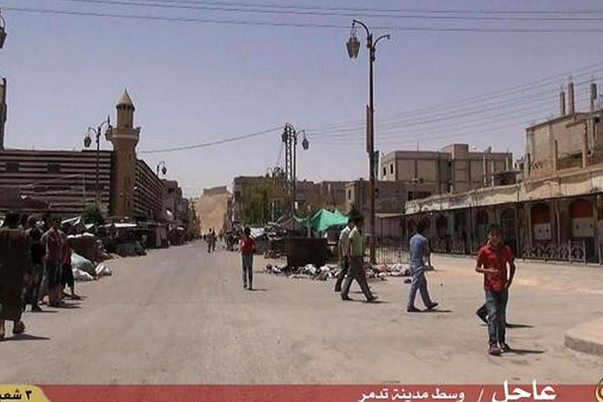 An image grab taken from a video made available by Jihadist media outlet Welayat Homs on May 21, 2015 allegedly shows people walking in a street of Syria's ancient city of Palmyra after the Islamic State in Iraq and Syria (ISIS) seized it. -- PHOTO: