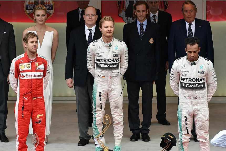 Winner Nico Rosberg (centre) of Germany, second-placed Ferrari driver Sebastian Vettel (left) of Germany and third-placed Mercedes driver Lewis Hamilton of Britain stand on the podium with Princess Charlene of Monaco (rear, second left), Prince Alber