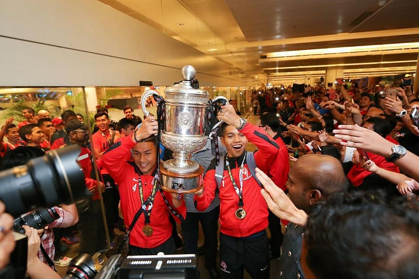 LionsXII captain Isa Halim and vice-captain Izwan Mahbud holding the Malaysian FA Cup trophy as the team enters the arrival hall of Changi Airport Terminal 2 on Sunday evening. -- ST PHOTO: ONG WEE JIN