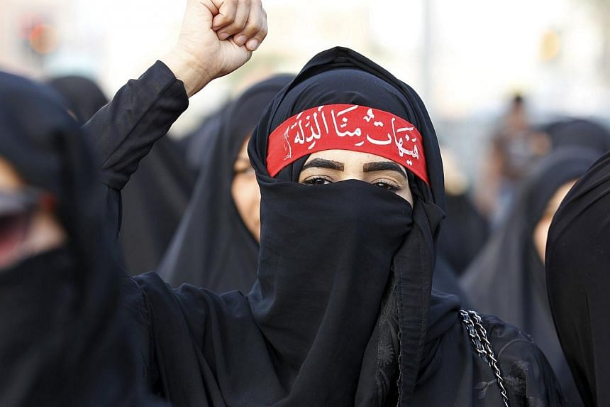 A protester shouts pro-Shi'ite slogans as she marches in the village of Sanabis, west of Manama, Bahrain, to show solidarity for victims of a suicide bomb attack in Saudi Arabia, May 23, 2015. -- PHOTO: REUTERS