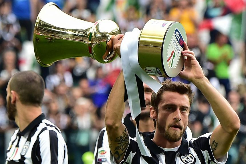 Juventus midfielder Claudio Marchisio holds the Cup as players present the Tim Cup trophy (Coppa Italia) to their fans prior their Serie A match against Napoli on May 23, 2015 at the Juventus stadium in Turin. Juventus won the Coppa Italia final matc