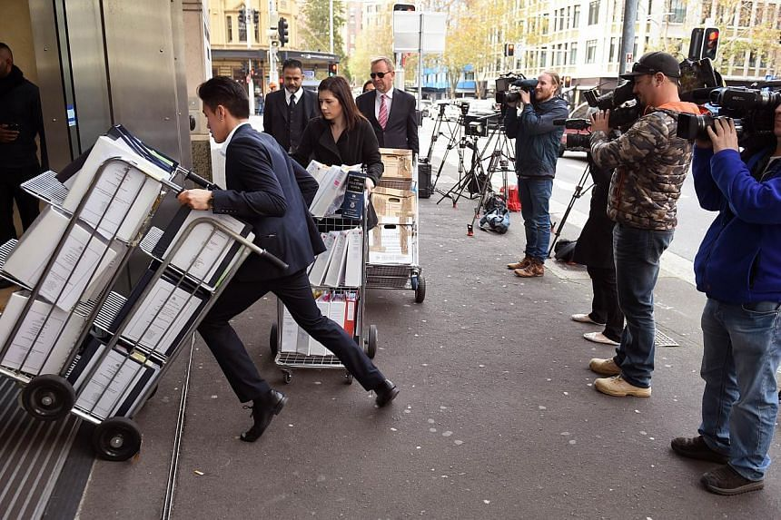 Television crews (right) film people entering the building in Sydney on May 25, 2015, where an inquest into the deaths arising from the Lindt Café siege is being held. -- PHOTO: AFP