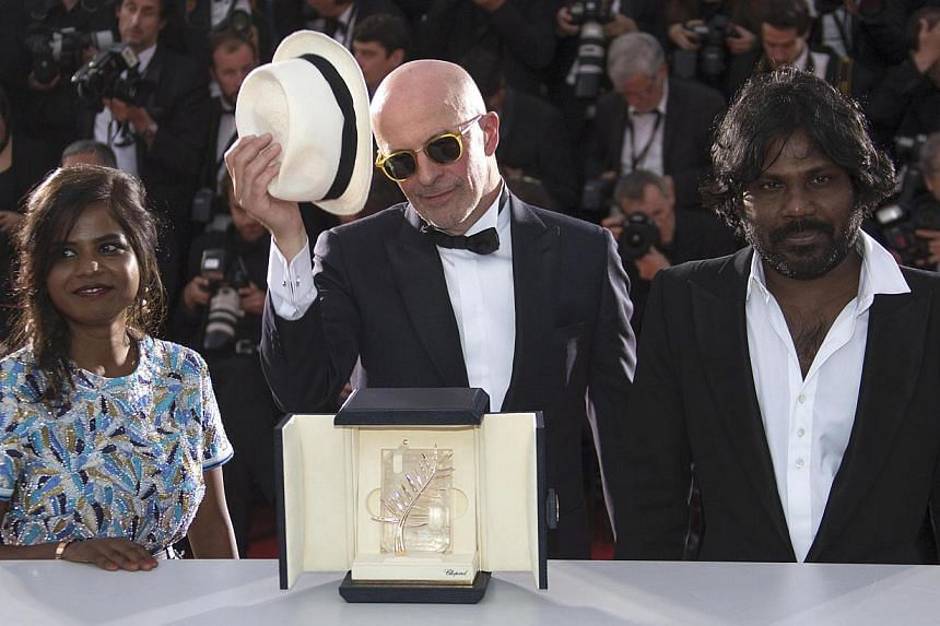 Director Jacques Audiard (centre), Palme d'Or award winner for his film Dheepan, actress Kalieaswari Srinivasan (left) and actor Jesuthasan Antonythasan pose during a photocall after the closing ceremony of the 68th Cannes Film Festival in southern F