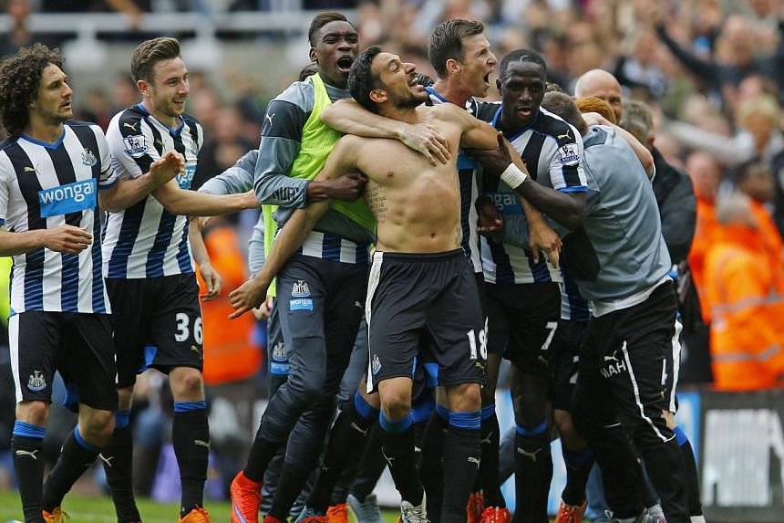 Jonas Gutierrez (centre, without shirt) celebrates with manager John Carver (right, in grey) and team mates after scoring the second goal for Newcastle United. -- PHOTO: REUTERS
