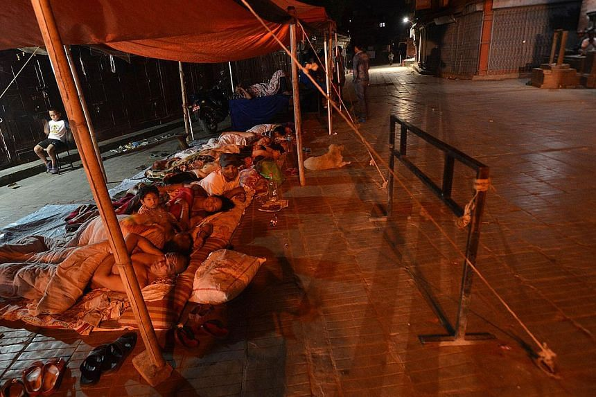 Nepalese residents sleep under an awning in Kathmandu on May 21, 2015, after multiple earthquakes struck the Himalayan nation. -- PHOTO: AFP