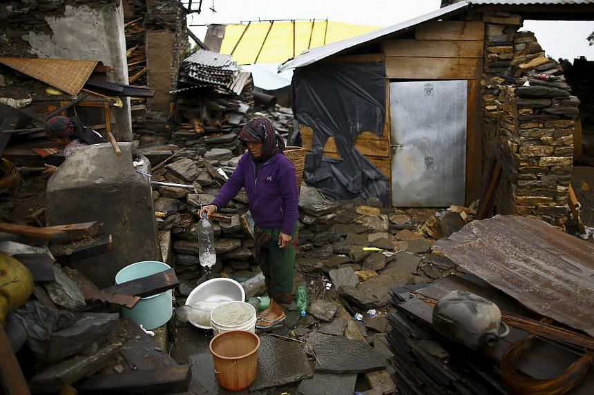 An earthquake victim fills water from a tap near the debris of a collapsed house at Barpak village at the epicentre of the April 25 earthquake in Gorkha district, Nepal, on May 21, 2015. -- PHOTO: REUTERS