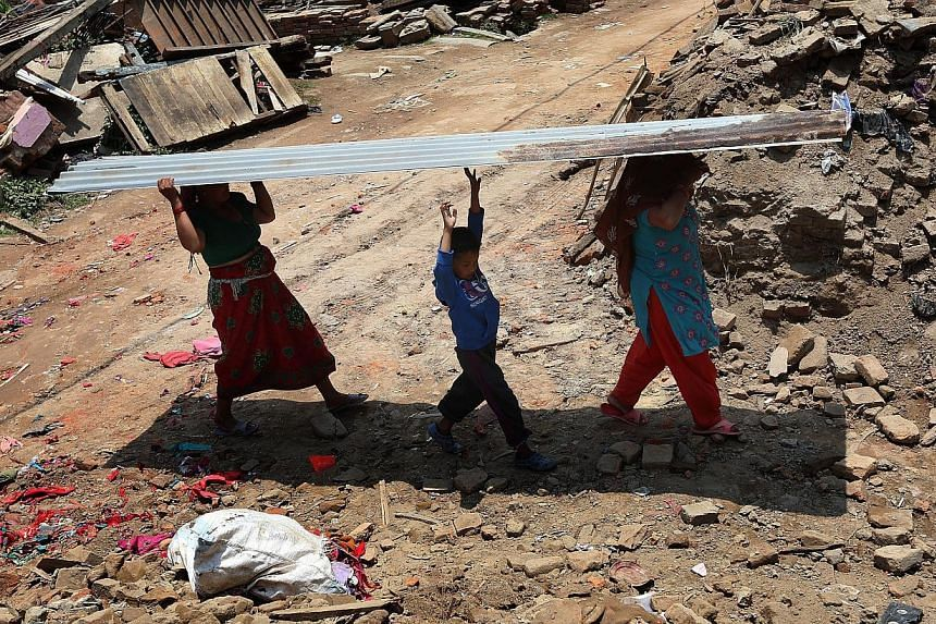 Nepalese earthquake survivors carry a metal sheet to build a temporary shelter in Sankhu on the outskirts of Kathmandu, Nepal on May 21, 2015. -- PHOTO: EPA