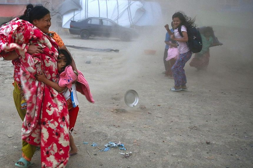 A storm whips through a tented area occupied by Nepalese earthquake survivors as a mother grabs her infant child and runs to find shelter in Kathmandu, Nepal, on May 23, 2015. -- PHOTO: EPA